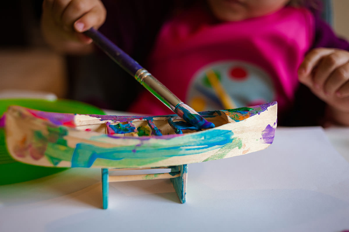 girl painting wooden boat