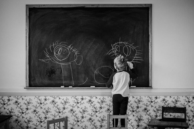 Boy drawing stick figures on chalkboard