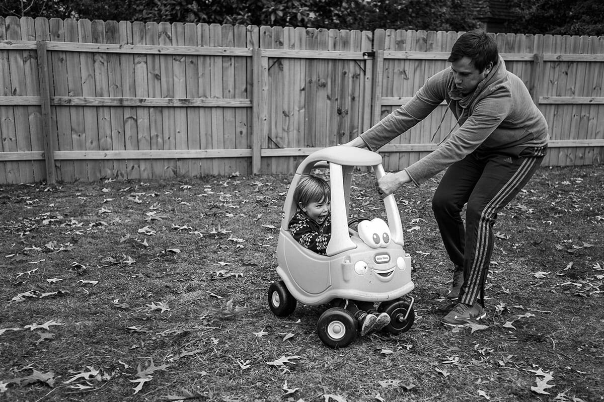 Father pushing boy in toy car