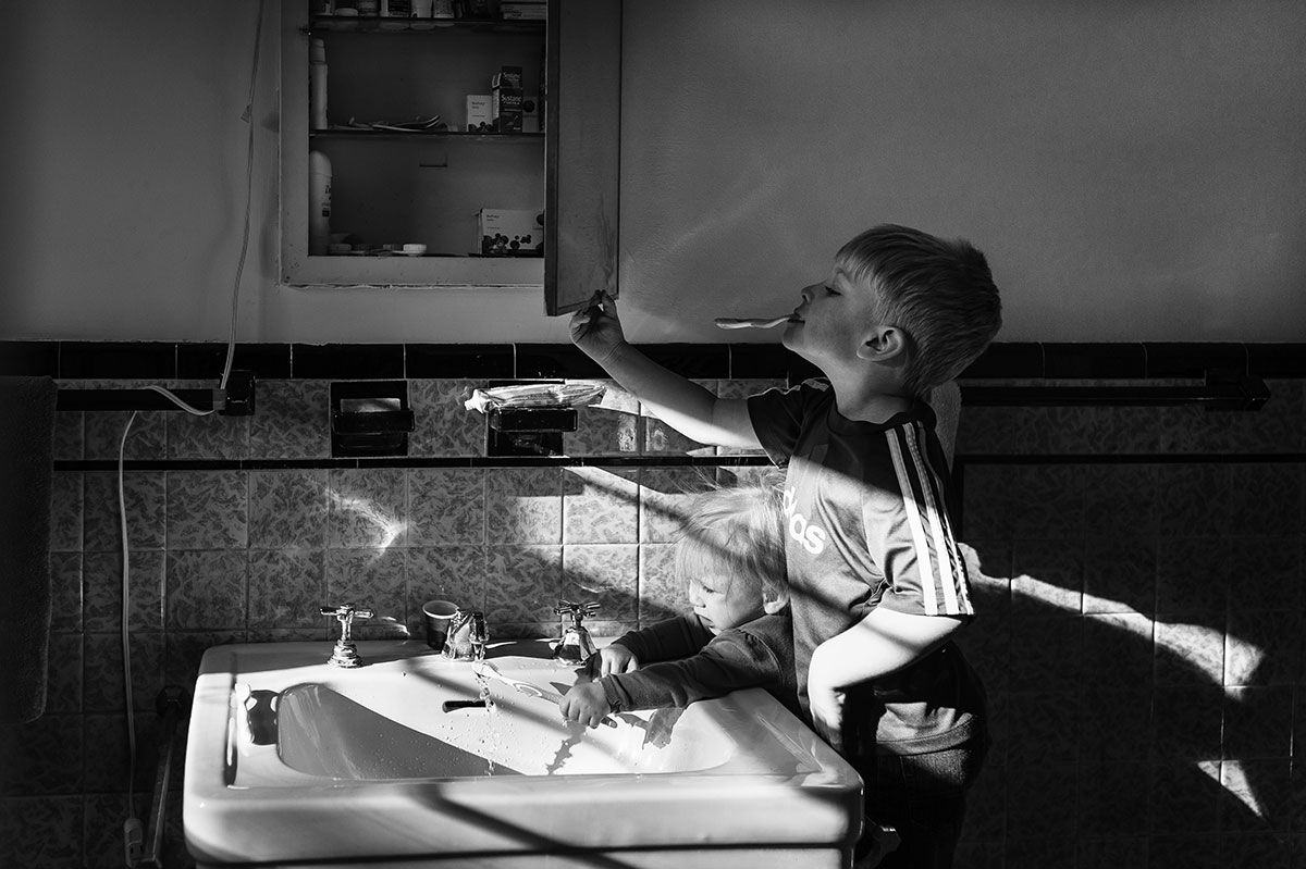 brother and sister brushing teeth, boy looking in mirror