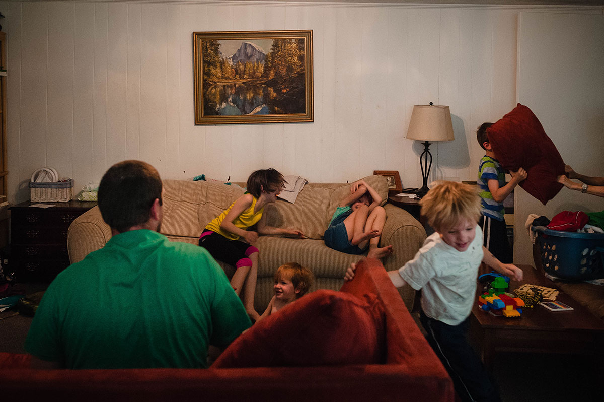 children pillow fighting, laughing, running, chaotic