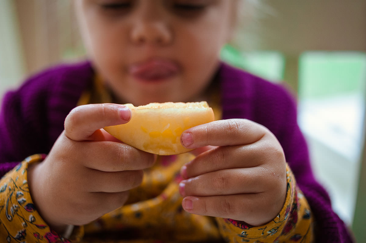 Girl licking lips looking at apple