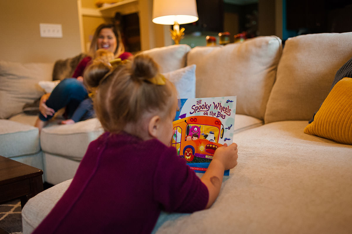 girl looking at halloween book
