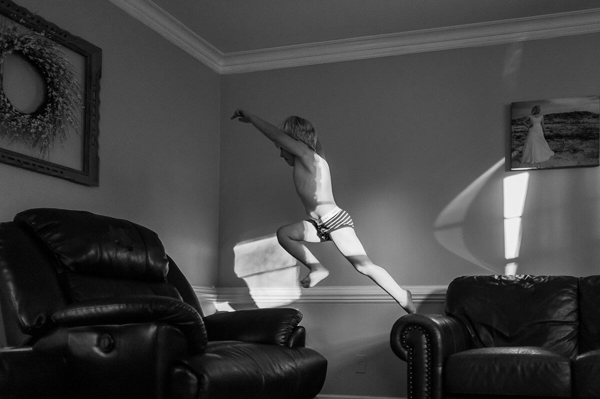 Boy jumping from couch to chair