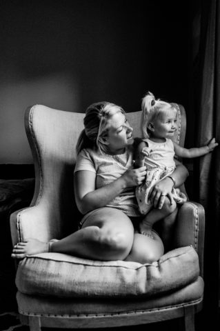 Mom sitting in chair holding daughters hand